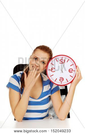 Tired yawning teenage woman holding clock