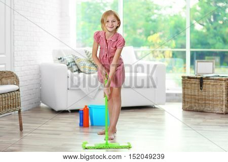Small girl cleaning room with mop on light background