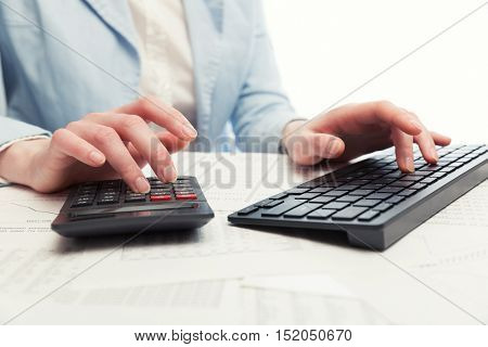 Financial accounting. Business woman using computer keyboard and calculator