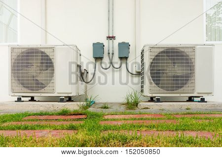 Air conditioning compressor installation outside building. Air conditioning system.