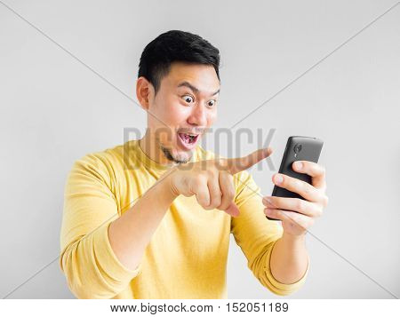 Asian man is playing mobile game in the smartphone.