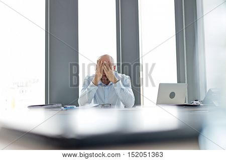 Tired mid adult businessman covering face at desk in office