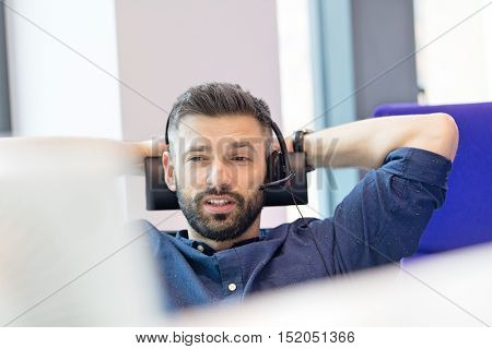 Mid adult businessman using headset in office