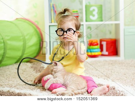 Child Girl Playing Doctor With A Cat Kitten In Nursery