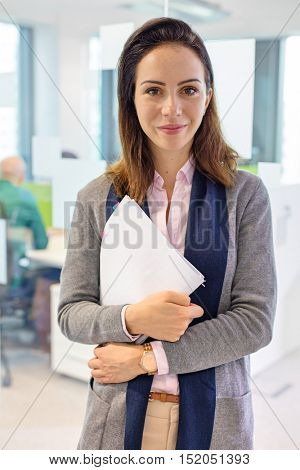 Portrait of confident young businesswoman holding book in office