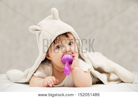 Portrait of baby girl playing with toy on blanket at home