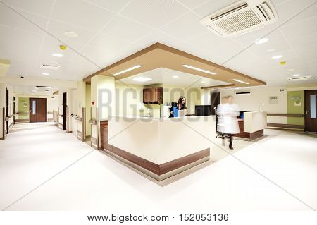 Reception in a modern hospital with a receptionist and a blurred doctor figure.