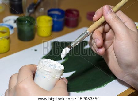 draws green tree gouache scoops the white paint from the jar with a brush hands drawing