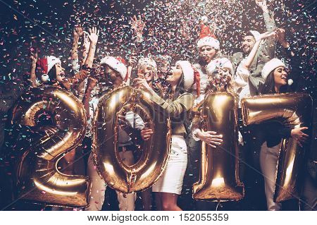 Happy New Year! Group of cheerful young people in Santa hats carrying gold colored numbers and throwing confetti