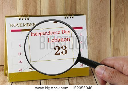 Magnifying glass in hand on calendar you can look Independence Day of Lebanon 23 November concept of a public relations campaign.
