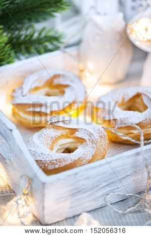 Cream puff rings (choux pastry) on white christmas background