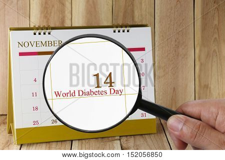 Magnifying glass in hand on calendar you can look World Diabetes Day in 14 November concept of a public relations campaign Life and Health.