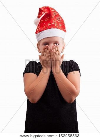 Christmas girl silent covers her mouth with his hands. Santa hat isolated portrait of a girl on a light background.