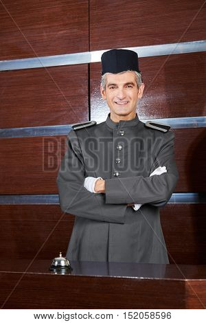 Friendly concierge in uniform at hotel reception with hotel bell