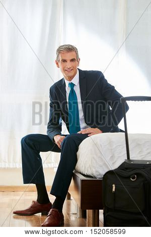 Smiling businessman with suitcase in a hotel room sitting on bed