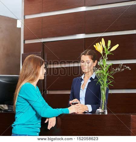 Woman paying with credt card hat hotel reception at check-out
