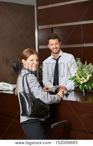 Woman paying with credit card in hotel at check-out