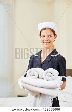 Smiling maid with fresh clean towels in hotel room during housekeeping