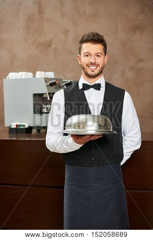 Waiter in uniform with food cloche in a hotel restaurant