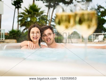 Young couple inside a jacuzzi and tasting wine