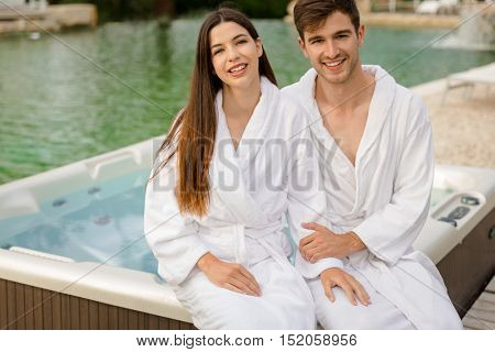 Young couple sitting near a jacuzzi in a luxury hotel