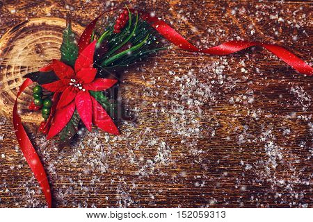 Christmas holiday wooden background with red poinsettia flower decoration and ribbon