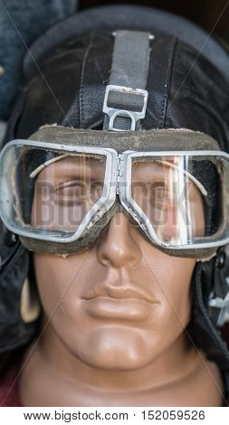 closeup shot of dummy man head with old vintage retro aircraft pilot leather flight helmet and goggles mask