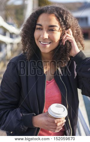 Beautiful happy mixed race African American girl teenager female young woman smiling drinking takeaway coffee outside wearing black bomber jacket