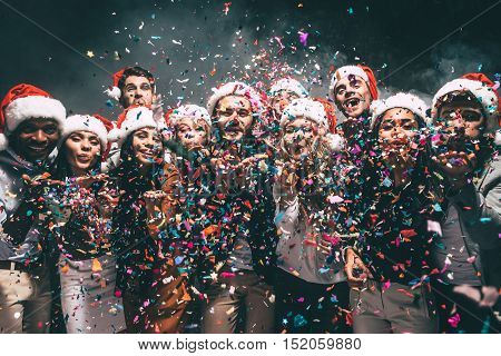 Colorful fun. Group of beautiful young people in Santa hats blowing colorful confetti and looking happy