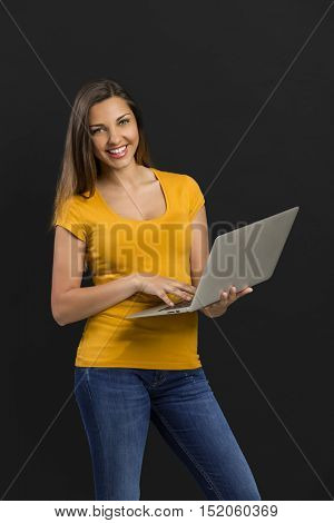 Beautiful woman in front of a black wall holding a laptop and pointing