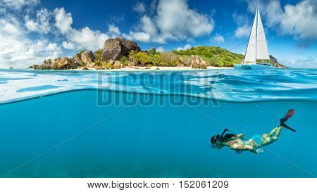 Young woman snorkling next to tropical island. Anchoring catamaran on background