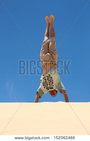 Man doing exersices standhand on dune in desert