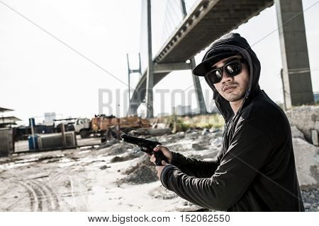 Gangster in hood and sunglasses changing clip of his pistol