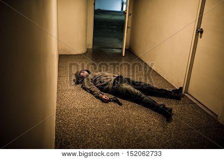 Killed gangster lying on the floor in corridor
