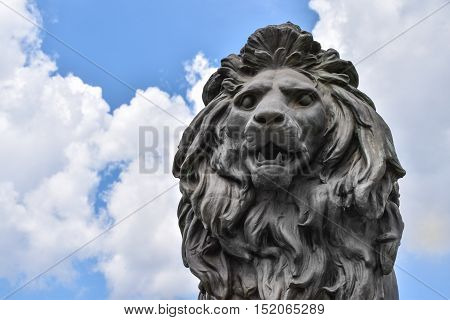Close-up of a lion's head statue on a cloudy background