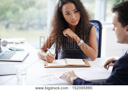 Pretty adviser taking notes when talking to client
