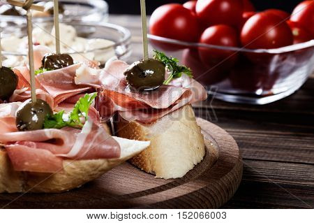 Spanish Tapas With Slices Jamon Serrano, Salami, Olives And Cheese Cubes On A Wooden Table