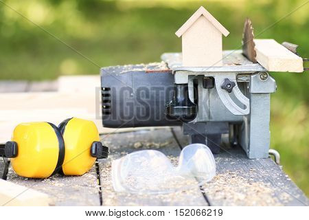 house model construction and saw on table outdoor