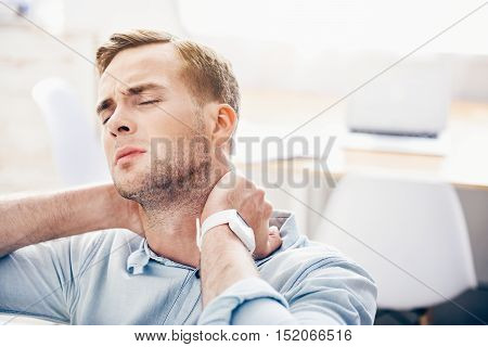 Moody sick man sitting on the couch and feeling ache while touching his neck
