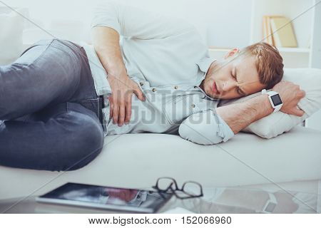 Get some rest. Young cheerless sick man lying on the couch and holding his hand on the stomach while having ache