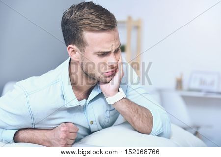 Acute pain. Good looking young exhausted man suffering from toothache and closing his eyes while sitting in the room.