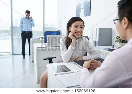 Smiling pretty business lady chatting with colleague