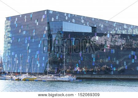 Reykjavik, Iceland - August 7, 2015: Harpa Concert Hall, the new Landmark of Reykjavik. Its located at the Harbor and was opened in May 2011. Boats in Front.