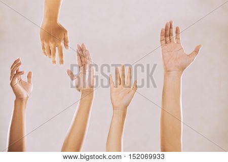 Hands of people reaching up for help