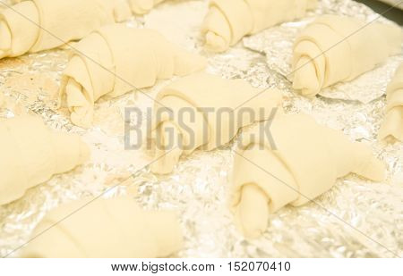 Several homemade raw croissants on the foil