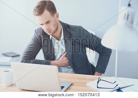 Feeling bad. Good looking young man suffering from heartache and working on laptop while sitting by the table.