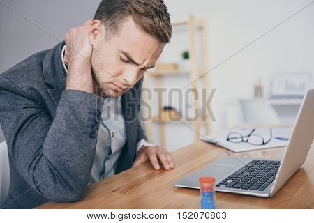 So tired.Unhappy young man suffering from pain in the neck and closing his eyes while working on laptop.