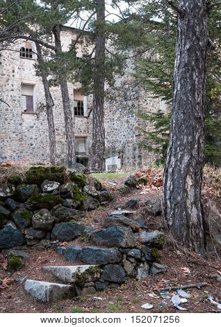 Exterior view of the abandoned hotel of Vereggaria at the forest of Troodos mountains in Cyprus with stoned stairs leading to the building.