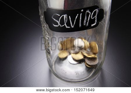 close up coins in a glass saving jar