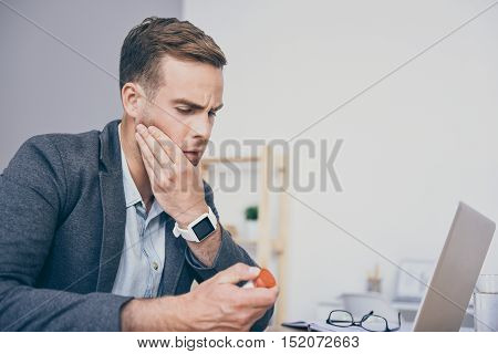 It must help. Handsome sad man holding medicines and using laptop while sitting by the table.